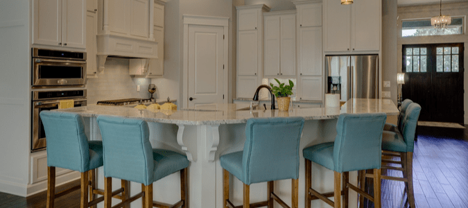 a white kitchen with blue barstools